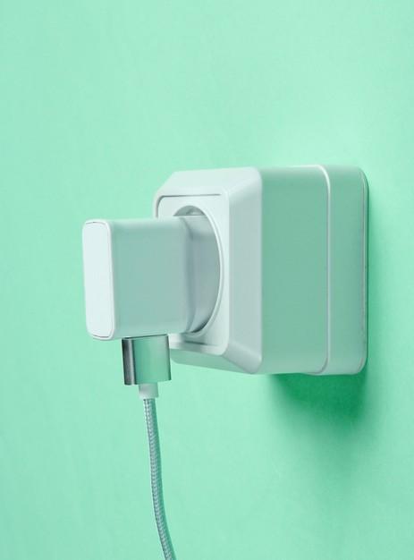 charger plugged into power outlet blue background 175682 13189 - 9 روش تشخیص شارژر اصلی از شارژر تقلبی